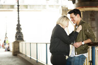 Young couple, standing underneath bridge, face to face, laughing - ISF02592