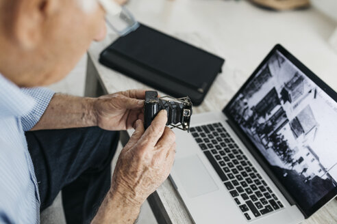 Senior man using laptop and holding his old photo camera, screen with old photo - JRFF01667