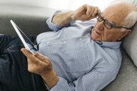 Senior man surfing the internet on a tablet while lying on the sofa - JRFF01670