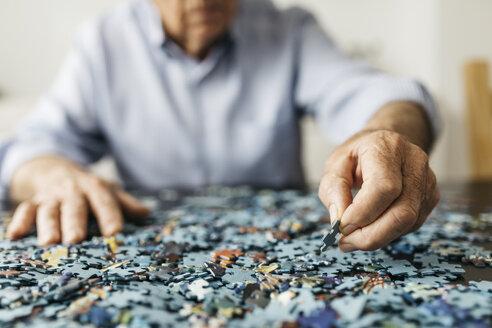 Senior man doing a jigsaw - JRFF01676