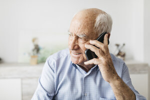 Happy senior man using smartphone at home - JRFF01679