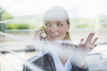Portrait of mature businesswoman on the phone waiting at platform - DIGF04475