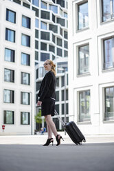 Mature businesswoman with suitcase walking in front of office buildings - DIGF04493