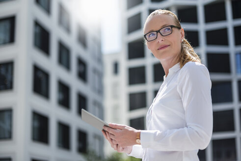 Portrait of businesswoman with tablet outdoors - DIGF04496