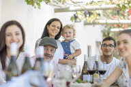 Family having lunch outdoors under grapevine trellis - ISF02767