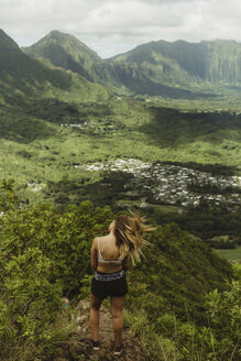 Rear view of woman on grass covered mountain, Oahu, Hawaii, USA - ISF02975