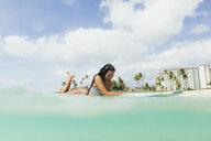 Surface level view of woman lying on surfboard, Oahu, Hawaii, USA - ISF02993