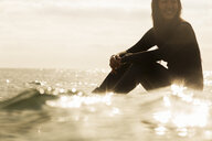 Young woman sitting in sea - ISF03014