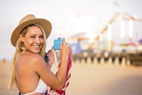 Portrait of young woman in bikini top photographing beach amusement park, Santa Monica, California, USA - ISF03041