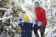 Man and son pointing while walking through snow covered forest - ISF03080