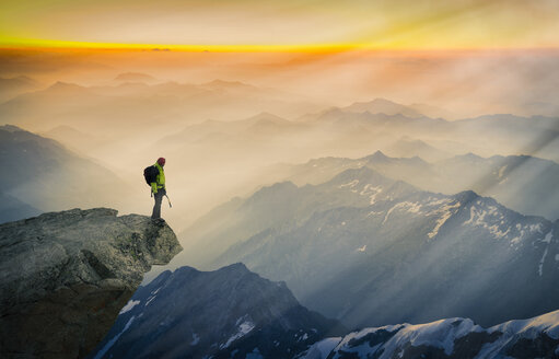 Mountain climber standing on  edge of mountain, looking at view, Courmayeur, Aosta Valley, Italy, Europe - ISF03167