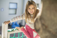 Girl at preschool, portrait on climbing frame in garden - ISF03221