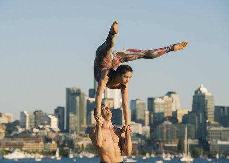 Teenage girl and young man, outdoors, woman balancing on man's hands in yoga position - ISF03224