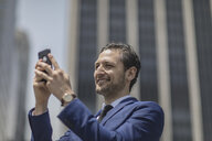 Smiling young businessman taking selfie outside office building, New York, USA - ISF03254
