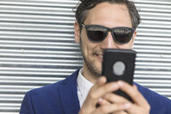 Young businessman in sunglasses looking at smartphone - ISF03257