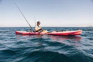 Young male sea kayaker looking at smartphone while fishing, Santa Cruz Island, California, USA - ISF03284