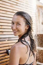 Portrait of young woman using outdoor shower, smiling - ISF03305