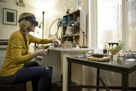 Female jewellery maker preparing metal in design studio - ISF03344