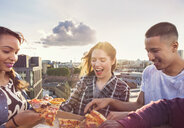Young adult friends sharing pizza at roof party in London, UK - ISF03428