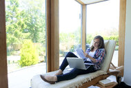 Young woman reclining on lounge chair by patio door reading paperwork - ISF03437