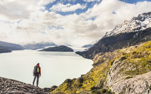 Male hiker looking out over Grey Lake and Glacier, Torres del Paine national park, Chile - ISF03455