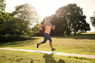 Young female runner running along park path in sunlight - ISF03479