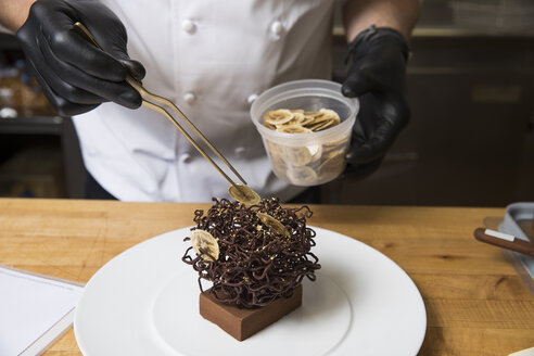 Chef placing slices of dried banana on chocolate nest cake decoration - ISF03563