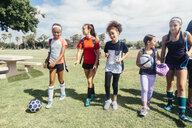 Schoolgirls walking to soccer practice on school sports field - ISF03569