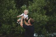 Mature man lifting up toddler son - ISF03635