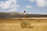 Woman standing on top of hay bale looking away - ISF03698