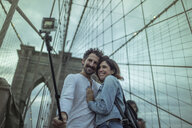 Couple on Brooklyn bridge taking selfie with selfie stick, New York, United States, North America - ISF03737