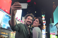 Couple taking selfie in Times Square, New York, United States, North America - ISF03743