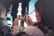 Woman taking photographing with smartphone in Times Square, New York, United States, North America - ISF03746