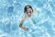 Overhead portrait of boy treading water in outdoor sunlit swimming pool - ISF03788