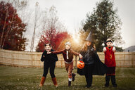 Portrait of boy and girls posed in halloween costumes in garden at sunset - ISF03815