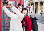 Two young stylish women taking selfie by red phone box, London, UK - ISF03821