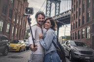 Couple taking photo with selfie stick, Brooklyn, New York, US - ISF03833