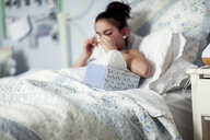 Girl in bed blowing nose on handkerchief - ISF03836