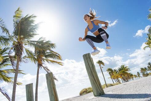 Young woman training, jumping mid air at beach - ISF03902