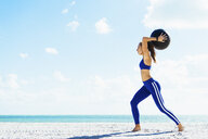 Young woman training, preparing to throw exercise ball on beach - ISF03905