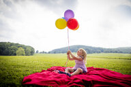 Girl sitting on red blanket in rural field looking up at bunch of colourful balloons - ISF03959