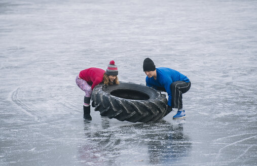 Couple flipping tyre on frozen lake - ISF03980