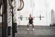 Woman lifting barbell in cross training gym - ISF04052