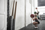 Friends throwing fitness ball against wall in cross training gym - ISF04073