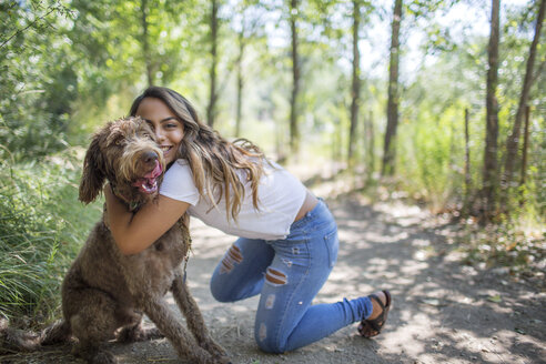 Portrait of teenage girl hugging cute dog on woodland path - ISF04157