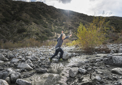 Boy leaping over rocks on riverbed - ISF04202