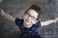 Portrait of girl wearing eye glasses looking up at camera - ISF04388