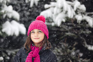 Girl in pink knitted hat looking up at falling snow - ISF04424