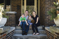 Portrait of parents sitting on porch steps with daughter and son - ISF04466