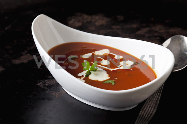 Bowl of tomato cream soup garnished with cream and parsley - CSF29191